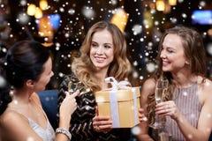 Femmes heureuses avec le champagne et le cadeau à la boîte de nuit Photographie stock libre de droits