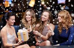 Femmes heureuses avec le champagne et le cadeau à la boîte de nuit Photos stock