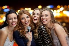 Femmes heureuses avec le microphone chantant au-dessus des lumières Photos libres de droits