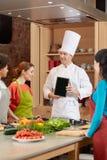Femmes heureuses avec le PC de chef et de comprimé dans la cuisine Image stock