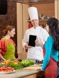 Femmes heureuses avec le PC de chef et de comprimé dans la cuisine Image libre de droits