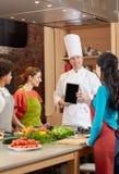 Femmes heureuses avec le PC de chef et de comprimé dans la cuisine Photo stock