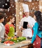 Femmes heureuses avec le PC de chef et de comprimé dans la cuisine Photo libre de droits