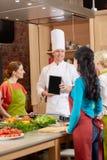 Femmes heureuses avec le PC de chef et de comprimé dans la cuisine Images libres de droits