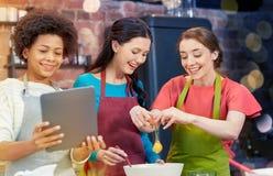 Femmes heureuses avec le PC de comprimé dans la cuisine Photos libres de droits