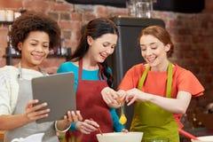 Femmes heureuses avec le PC de comprimé dans la cuisine Photographie stock