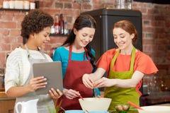 Femmes heureuses avec le PC de comprimé dans la cuisine Photographie stock libre de droits