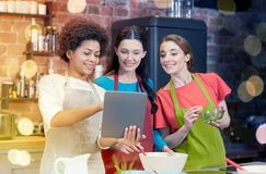 Femmes heureuses avec le PC de comprimé faisant cuire dans la cuisine Photo libre de droits
