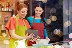 Femmes heureuses avec le PC de comprimé faisant cuire dans la cuisine Images stock