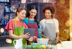 Femmes heureuses avec le PC de comprimé faisant cuire dans la cuisine Image libre de droits