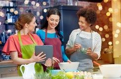 Femmes heureuses avec le PC de comprimé faisant cuire dans la cuisine Photographie stock libre de droits