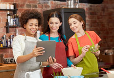 Femmes heureuses avec le PC de comprimé faisant cuire dans la cuisine Photos stock