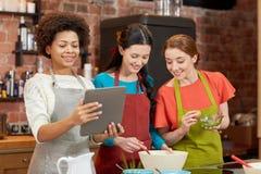 Femmes heureuses avec le PC de comprimé faisant cuire dans la cuisine Photo stock
