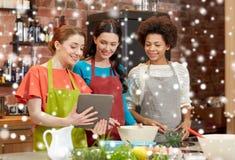 Femmes heureuses avec le PC de comprimé faisant cuire dans la cuisine Photos libres de droits