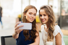 Femmes heureuses avec le smartphone prenant le selfie au café Photos stock