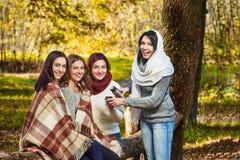 Femmes heureuses avec le thé en parc Photographie stock libre de droits
