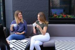 Femmes heureuses buvant du café au café et au repos Image stock