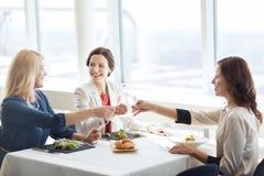 Femmes heureuses buvant du champagne au restaurant Image stock