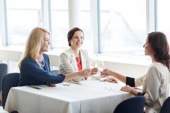 Femmes heureuses buvant du champagne au restaurant Photographie stock libre de droits