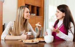 Femmes heureuses buvant le thé et le bavardage Photo stock