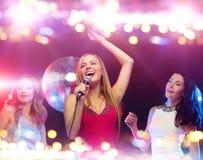 Femmes heureuses chantant le karaoke et la danse Photos libres de droits