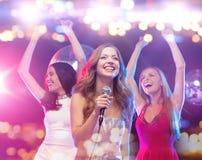 Femmes heureuses chantant le karaoke et la danse Photographie stock