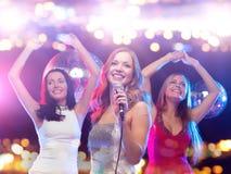 Femmes heureuses chantant le karaoke et la danse Image stock
