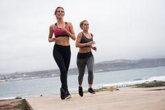 Femmes heureuses courant sur le boarwalk Photographie stock libre de droits