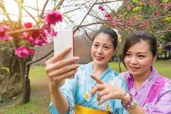 Femmes heureuses d'amies portant l'habillement de kimono Photos stock