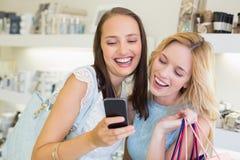 Femmes heureuses d'amis regardant le smartphone Photo stock