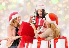 Femmes heureuses dans des chapeaux de Santa avec des cadeaux de Noël Image stock