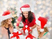 Femmes heureuses dans des chapeaux de Santa avec des cadeaux de Noël Photographie stock libre de droits