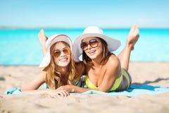 Femmes heureuses dans des chapeaux prenant un bain de soleil sur la plage Photos stock
