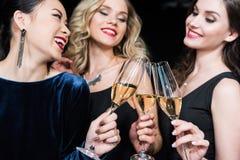 Femmes heureuses dans des robes élégantes faisant tinter des verres avec le champagne Photo libre de droits