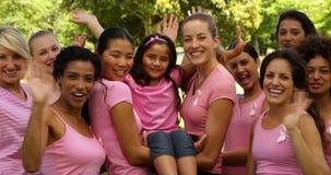 Femmes heureuses dans le rose pour la conscience de cancer du sein en parc ondulant à l'appareil-photo banque de vidéos