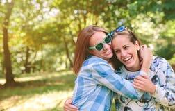 Femmes heureuses embrassant et ayant l'amusement au-dessus de la nature Photo stock