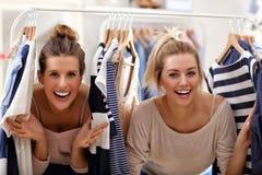 Femmes heureuses faisant des emplettes pour des vêtements Photographie stock libre de droits