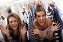 Femmes heureuses faisant des emplettes pour des vêtements Photo stock