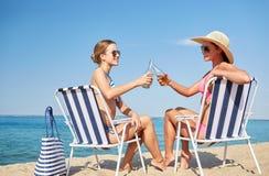 Femmes heureuses faisant tinter des bouteilles et buvant sur la plage Photos stock