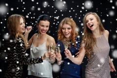 Femmes heureuses faisant tinter des verres de champagne au-dessus de neige Images stock