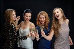 Femmes heureuses faisant tinter des verres de champagne au-dessus de noir Images libres de droits