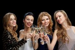 Femmes heureuses faisant tinter des verres de champagne au-dessus de noir Photos libres de droits