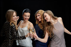 Femmes heureuses faisant tinter des verres de champagne au-dessus de noir Photos stock