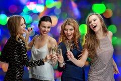 Femmes heureuses faisant tinter des verres de champagne au-dessus des lumières Photo stock