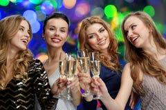 Femmes heureuses faisant tinter des verres de champagne au-dessus des lumières Photos stock