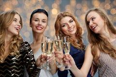 Femmes heureuses faisant tinter des verres de champagne au-dessus des lumières Photos libres de droits