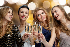 Femmes heureuses faisant tinter des verres de champagne au-dessus des lumières Images libres de droits
