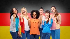 Femmes heureuses internationales au-dessus de drapeau allemand Photographie stock