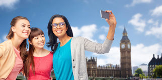Femmes heureuses internationales prenant le selfie à Londres Photos stock
