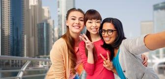 Femmes heureuses internationales prenant le selfie dans la ville Image libre de droits